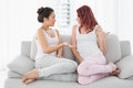 Relaxed female friends chatting in living room young the at home Royalty Free Stock Photo