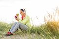 Relaxed fitness woman eating apple after workout and texting sms on smartphone during a break at beach on summer sunset sporty Stock Photo