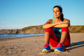 Relaxed fitness woman resting at beach after exercising and watching the sun on summer sunset Stock Photo