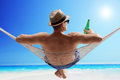 Relaxed guy lying in a hammock and drinking beer young on sunny beach by the ocean Stock Photos