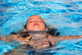 Relaxed kid girl at the pool face in water surface Royalty Free Stock Photo