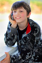 Relaxed kid talking happy young boy with dark hair wearing a camouflage jacket leaning against a deck railing on a phone shallow Royalty Free Stock Photography