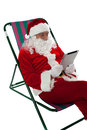 Relaxed male santa operating tablet device claus relaxing and using touch pad Royalty Free Stock Image