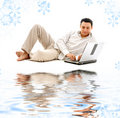 Relaxed man with laptop on white sand Royalty Free Stock Image