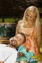 Relaxed man lying in lap of happy woman at picnic smiling casual men laying romantic blonde women outdoor Royalty Free Stock Photos