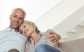 Relaxed mature couple sitting on sofa smiling at home Stock Images