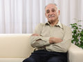 Relaxed old man at home disengaged sitting on the sofa hands folded indoor Stock Photography