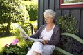 Relaxed old woman reading newspaper sitting on bench in backyard Royalty Free Stock Photos