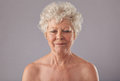 Relaxed old woman in thought close up of on grey background with her eyes closed naked senior female against grey background Royalty Free Stock Image