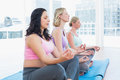 Relaxed pregnant women meditating in yoga class a fitness studio Royalty Free Stock Image