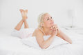 Relaxed pretty woman with joined hands in bed young lying at home Stock Photos