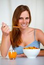 Relaxed pretty young woman eating breakfast Royalty Free Stock Image