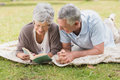 Relaxed senior couple reading book while lying in park smiling the Stock Photo