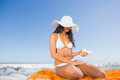 Relaxed sexy woman applying sun cream while sitting on her towel the beach Royalty Free Stock Photos