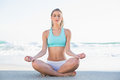 Relaxed slender blonde in sportswear meditating on a sunny beach Royalty Free Stock Images