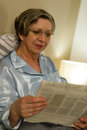 Relaxed smiling mature woman reading newspaper in bed at home Royalty Free Stock Image