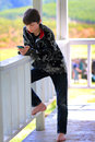 Relaxed tween texting happy young boy with dark hair wearing a camouflage jacket leaning against a deck railing on a phone shallow Royalty Free Stock Photos