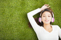 Relaxed woman listening to the music with headphones lying on grass Stock Photo