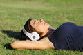 Relaxed woman listening to the music with headphones lying on the grass of a garden Royalty Free Stock Photo