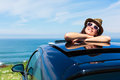 Relaxed woman on summer car vacation travel day dreaming leaning out sunroof towards the sea Royalty Free Stock Photo
