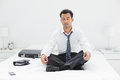 Relaxed young businessman sitting in lotus pose on bed full length of a at home Stock Images