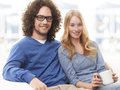 Relaxed young couple spending time together sitting on couch Royalty Free Stock Images