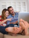 Relaxed young couple working on laptop computer at home happy modern indoor Stock Images