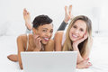 Relaxed young female friends using laptop in bed portrait of happy at home Royalty Free Stock Photos