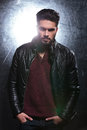 Relaxed young man with long beard wearing leather jacket posing for the camera Royalty Free Stock Images
