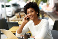 Relaxed young woman at cafe talking on cell phone Royalty Free Stock Photo