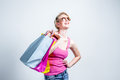 Relaxed young woman with shopping bags on grey background Stock Images