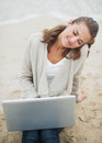 Relaxed young woman sitting on lonely beach with laptop in sweater Royalty Free Stock Images