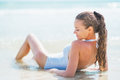 Relaxed young woman in swimsuit laying at seaside rear view pretty white Stock Image