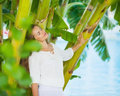 Relaxed young woman among tropical palms Stock Images