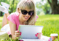 Relaxed young woman using tablet computer outdoors lying on grass and Royalty Free Stock Images