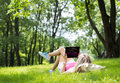 Relaxed young woman using tablet computer outdoors lying on grass and Royalty Free Stock Photo