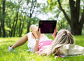 Relaxed young woman using tablet computer outdoors lying on grass and Royalty Free Stock Photos