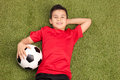 Relaxed youngster lying on pitch and holding a football in red jersey in his hand looking at the camera Stock Photography