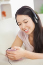 Relaxing asian girl lying on the sofa and listening to music wit with smartphone at home in sitting room Royalty Free Stock Image