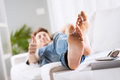 Relaxing barefoot young man on sofa in the living room close up Stock Images