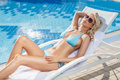 Relaxing on the deck chair beautiful young women relaxing on th woman near pool Royalty Free Stock Image