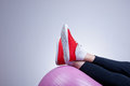Relaxing with fitness ball female legs wearing red trainers kept on purple after workout Stock Image