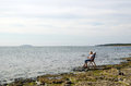 Relaxing at flat rock coast woman in a chair a Royalty Free Stock Photos