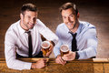 Relaxing at friday night top view of two cheerful young men in shirt and tie holding glasses with beer and smiling while sitting Stock Photos