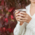 Relaxing girl drinks tea in autumn park close up Stock Image