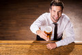 Relaxing with glass of fresh beer top view handsome young man in shirt and tie holding and smiling while sitting at the bar Royalty Free Stock Image