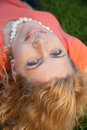 Relaxing in grass. Top view of beautiful young woman holding hands behind head and smiling to you Royalty Free Stock Photo
