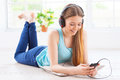 Relaxing with her favorite music cheerful teenage girl in headphones listening to the while lying down on the floor at apartment Royalty Free Stock Images