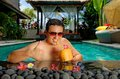 Relaxing holiday handsome man relaxing swimming pool drinking coconut cocktail luxury villa bali island Royalty Free Stock Image