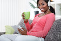 Relaxing at home smiling black woman with music and tea Royalty Free Stock Photography